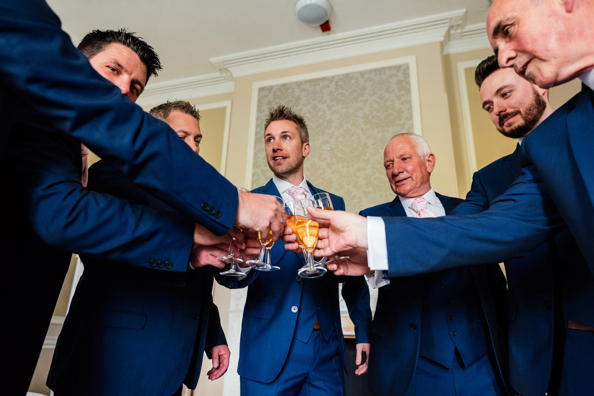 groom with his father and groomsmen having a drink