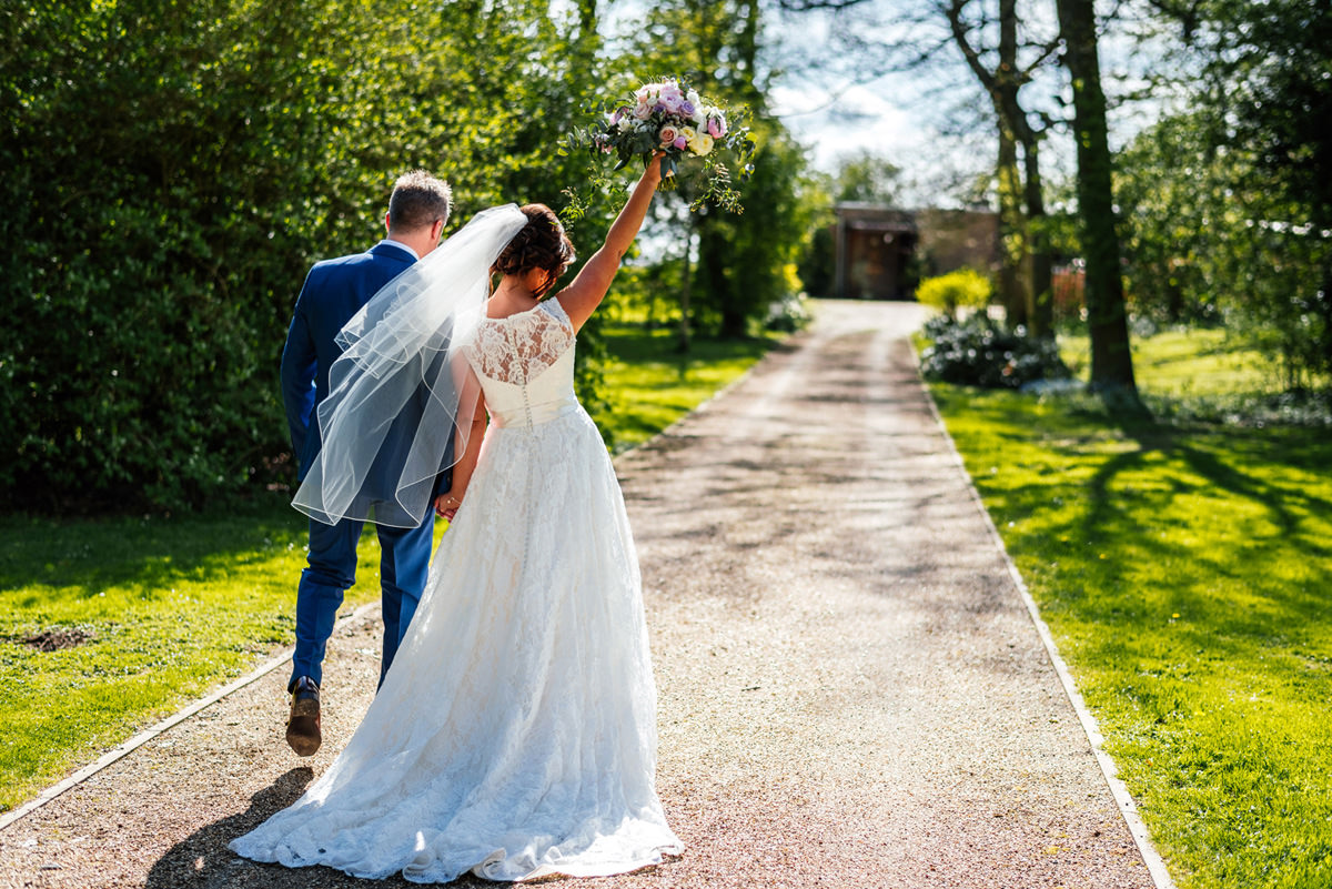 bride and groom walking away with bouquet high in the air