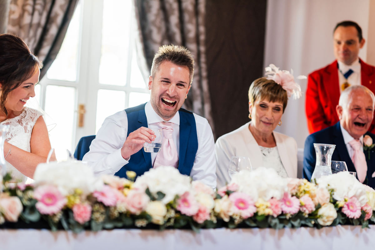 groom laughing at the wedding speeches
