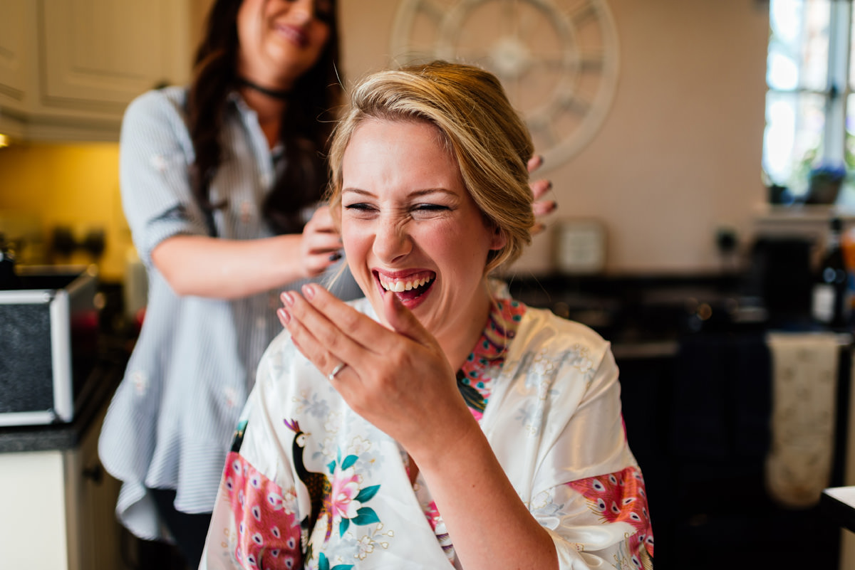 emily laughing during hair and make up on the morning of her wedding