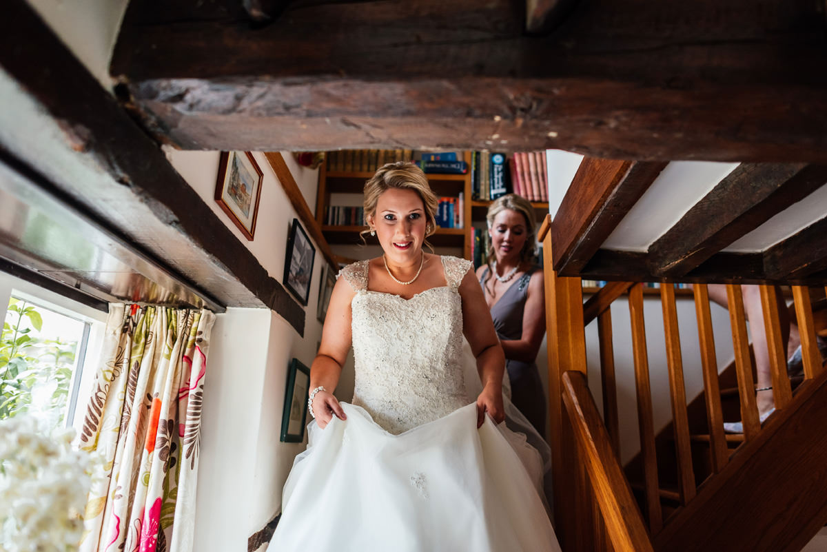 bride coming down stairs in her wedding dress