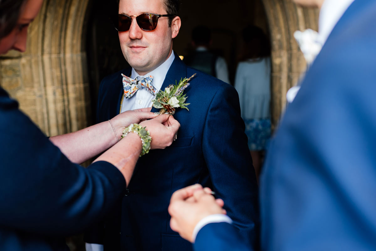 groom is helped putting his button hole on