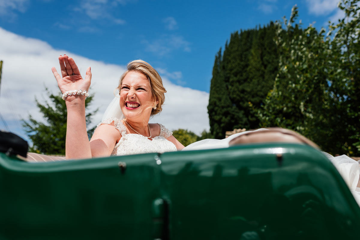 bride waves from the wedding car when she arrives at the church
