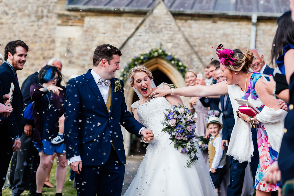 guest tries to get confetti down bride's dress