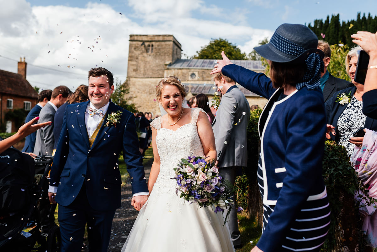 Emily & Simon walk from church with guests throwing confetti