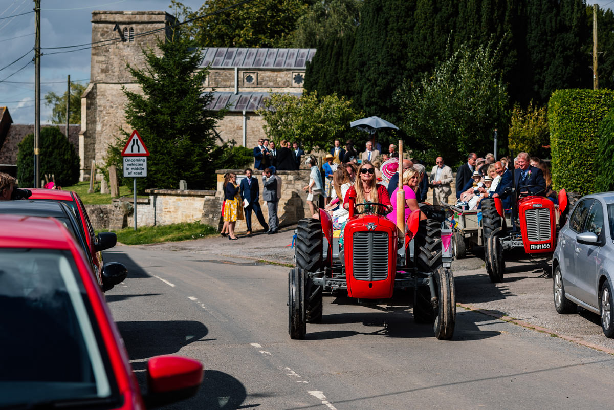 red vintage tractors bring guests from the church to the marquee