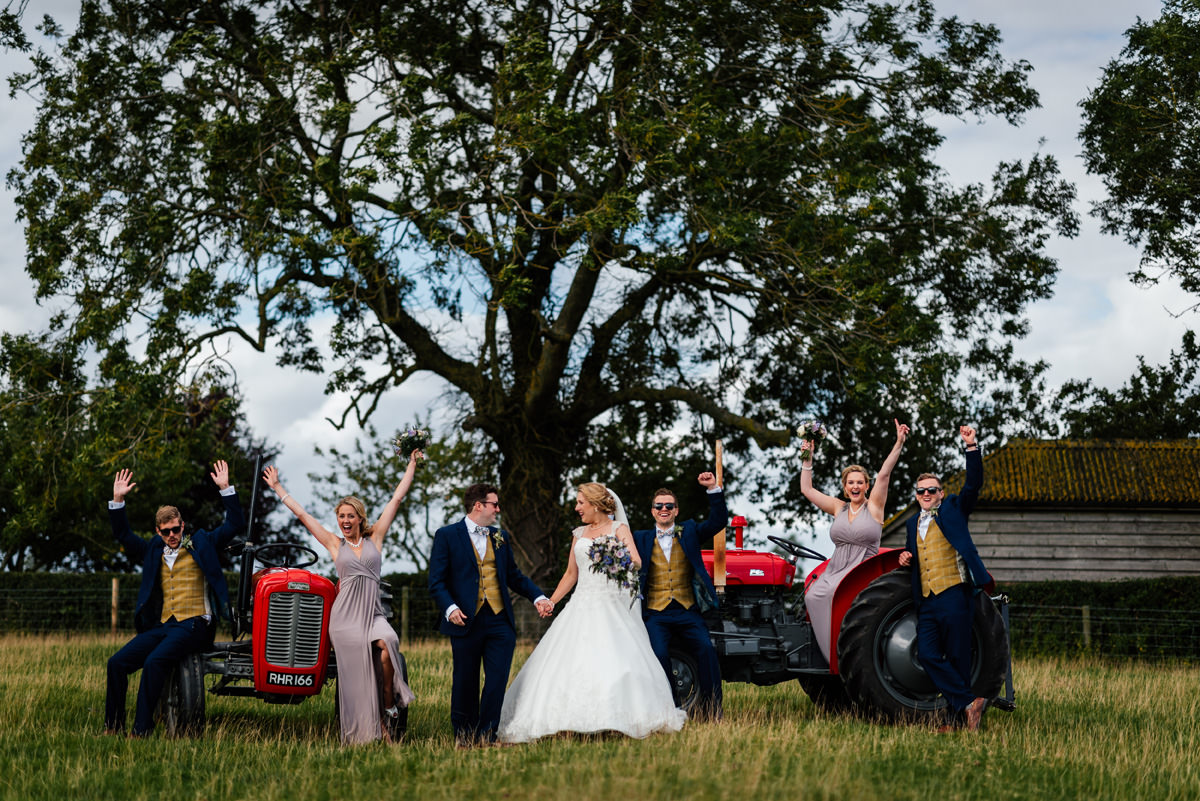 full group photo of bridal party with vintage tractors