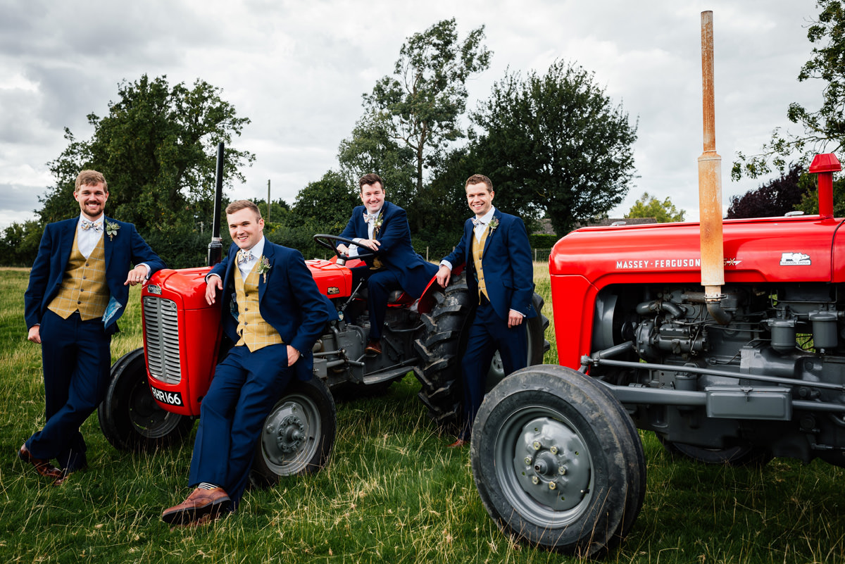 group photo of groomsmen with vintage tractors