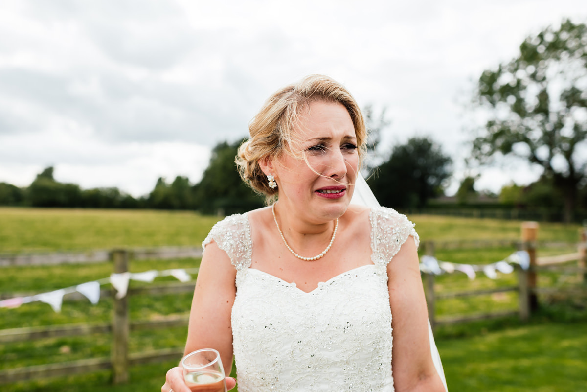 bride pulling face after drinking a shot of alcohol