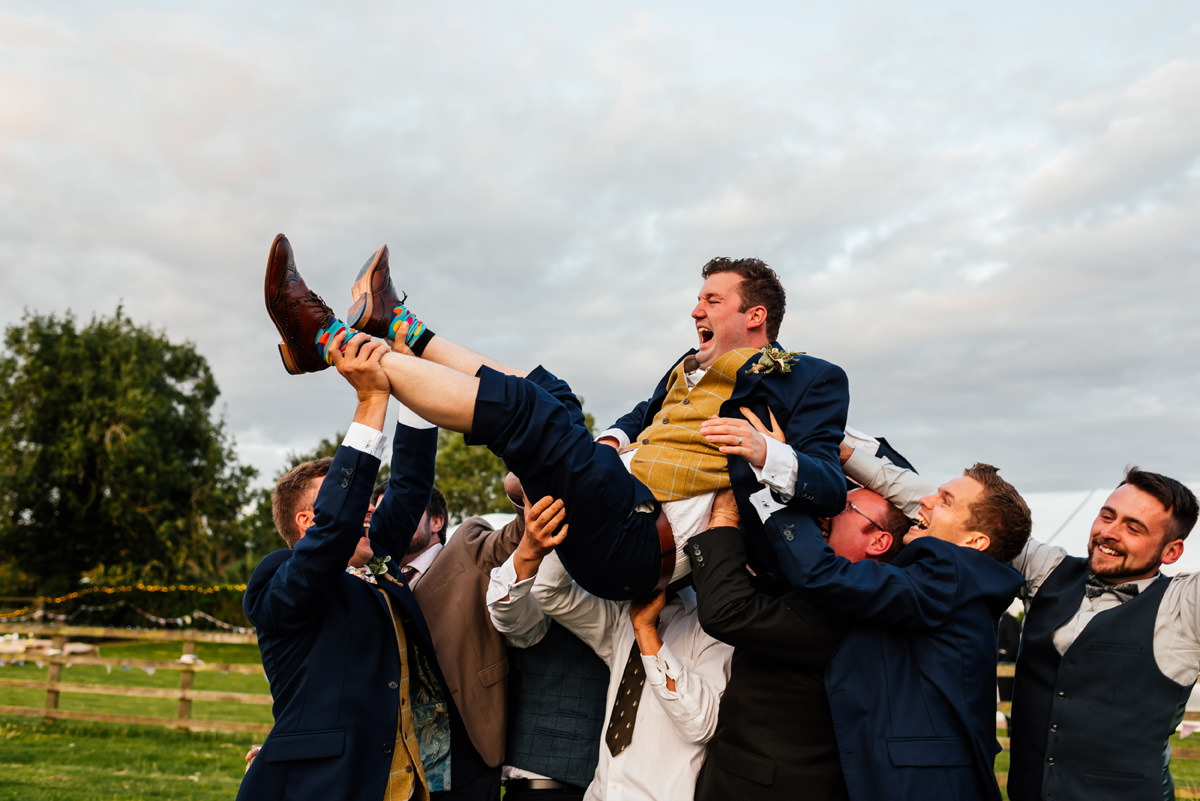 groom being lifted by his friends