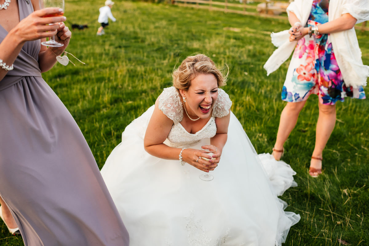 bride laughing during group photos on wedding day
