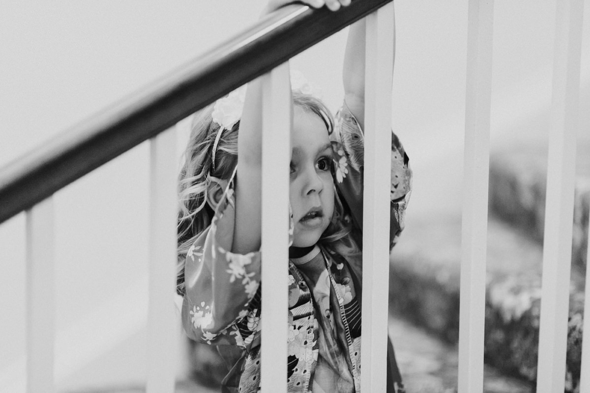 flower girls looks on through stairs