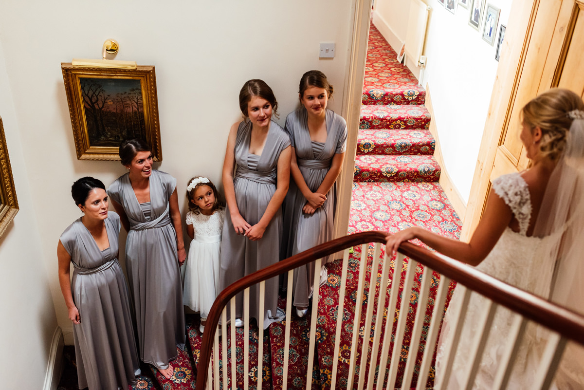 bridesmaids and flower girls see bride in her wedding dress for the first time