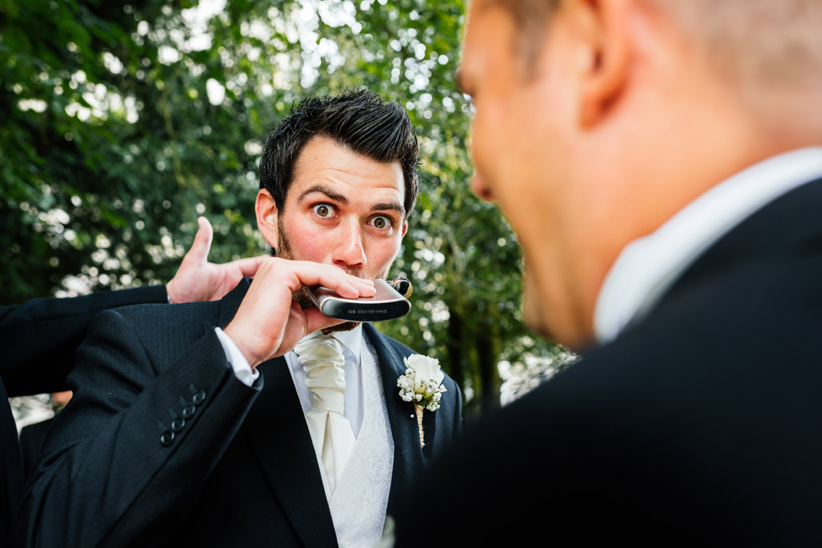 groom has a quick cheeky swig of alcohol before the marriage ceremony