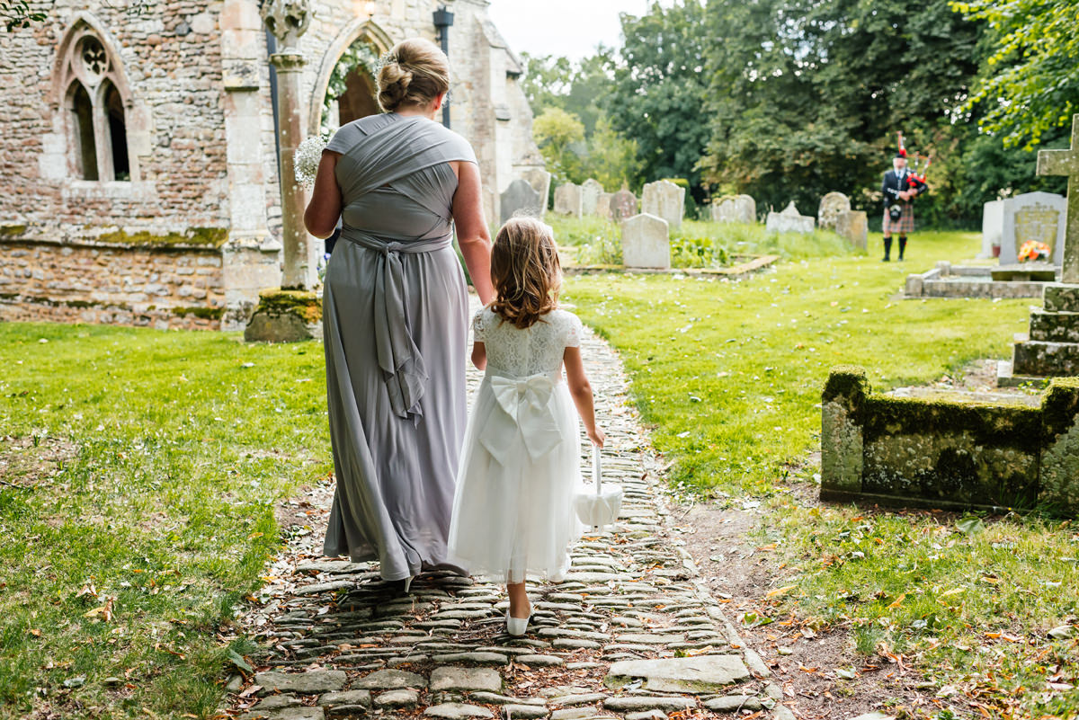 bridesmaid and flower girl walk to the church