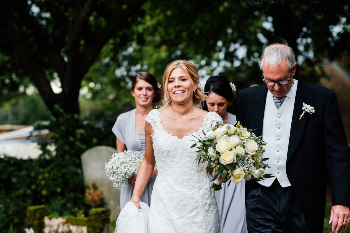 bride arrives at the church with bridal party and father of the bride