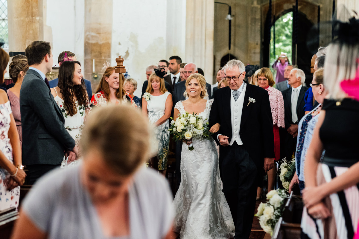 bride and father of the bride walk down the aisle in church ceremony