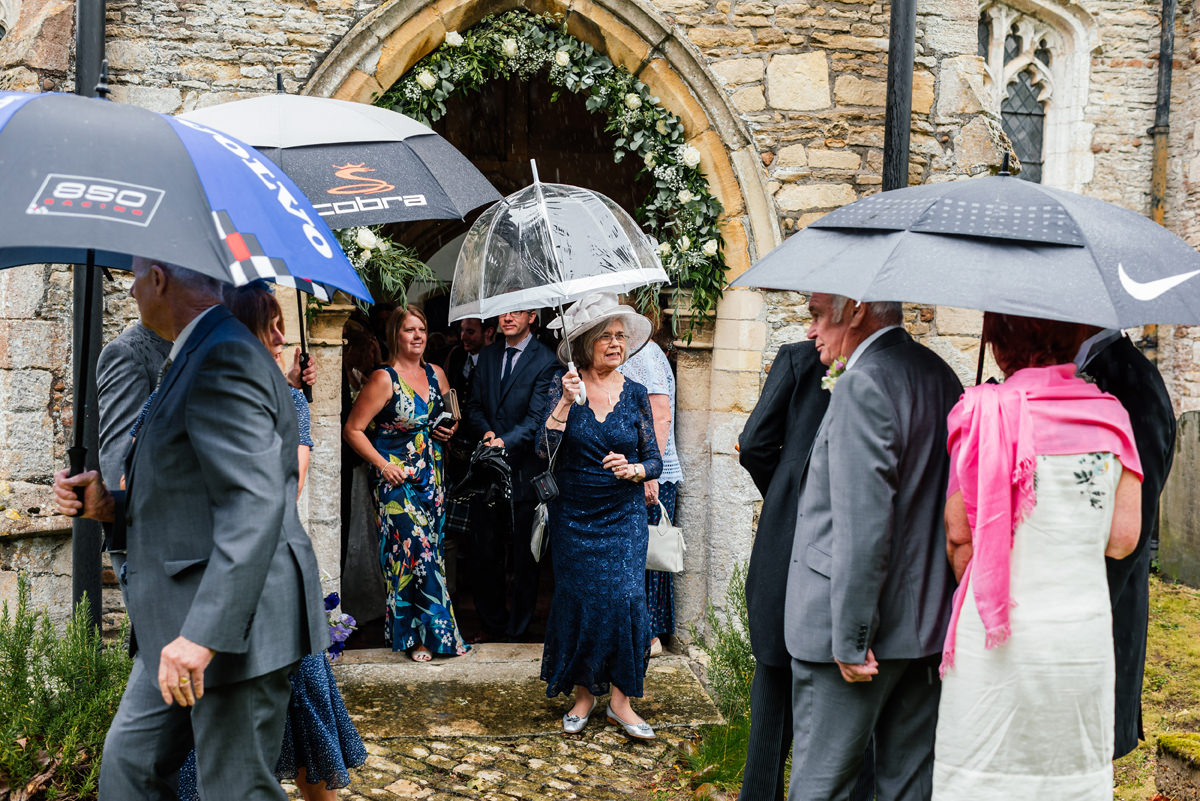 wedding guests leaving the church with umbrellas in the rain