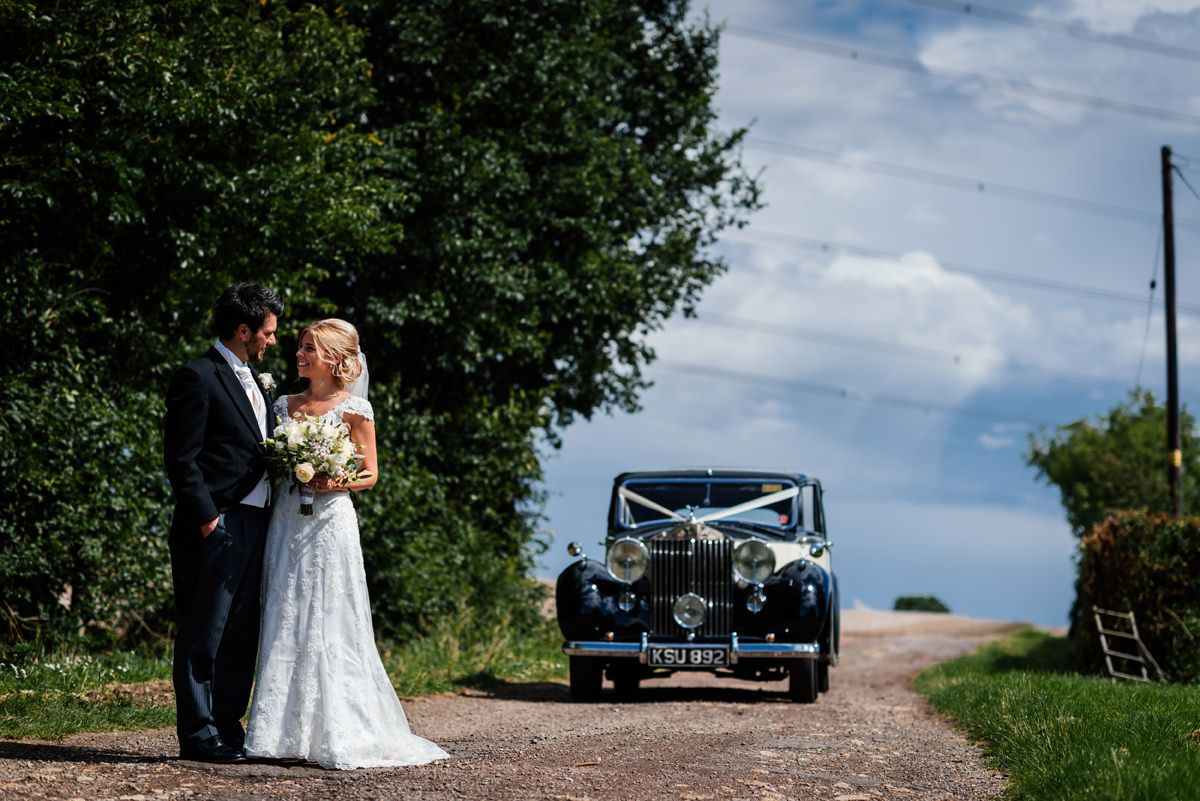bride and groom portrait with vintage wedding car