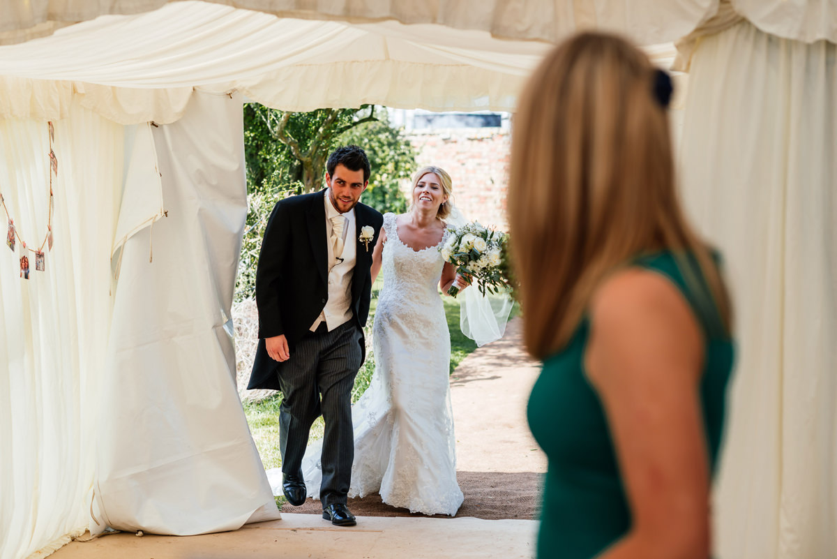 Bride and groom enter the wedding breakfast marquee