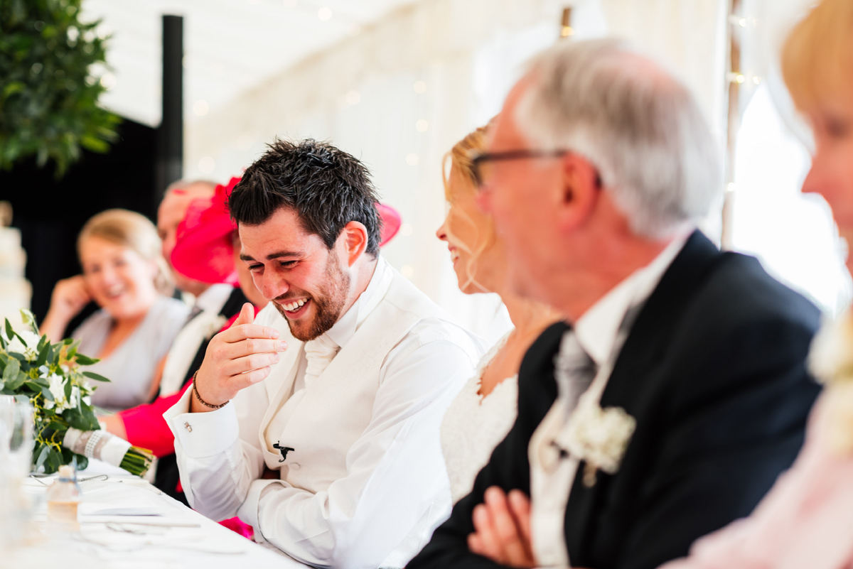 groom laughing during the best man speech