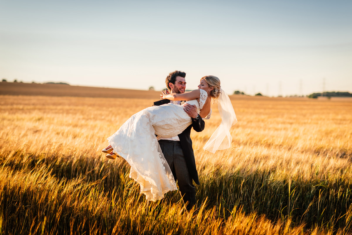 groom carries his bride through a golden field