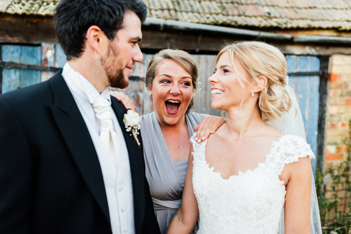 bridesmaid photobombs bride and groom portrait