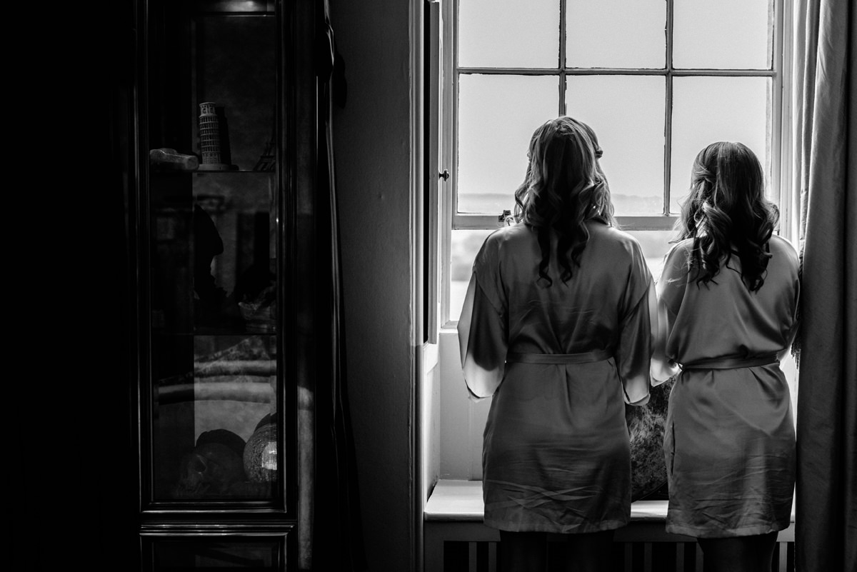 bridesmaids looking out side of the window during bridal prep