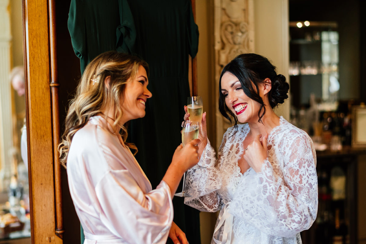 bride and bridesmaid having champagne