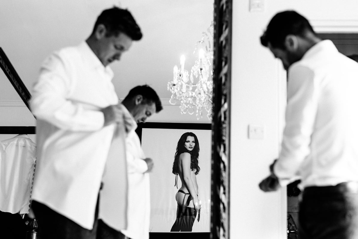 groomsmen prep with photo of Kate Moss watching them