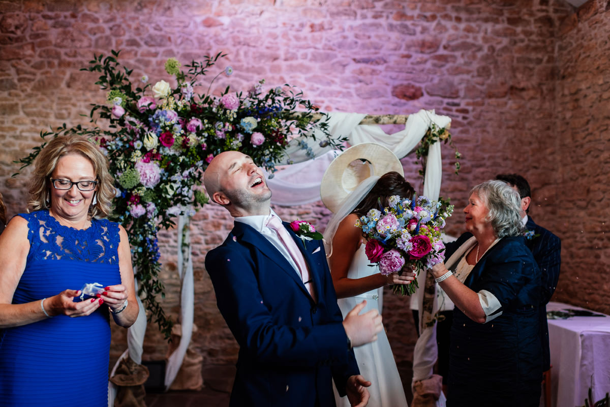 groom gets confetti thrown in his face after the ceremony