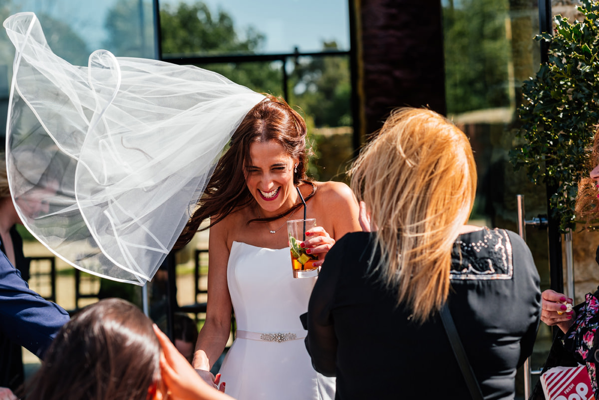 bride enjoys a drink with wedding guests