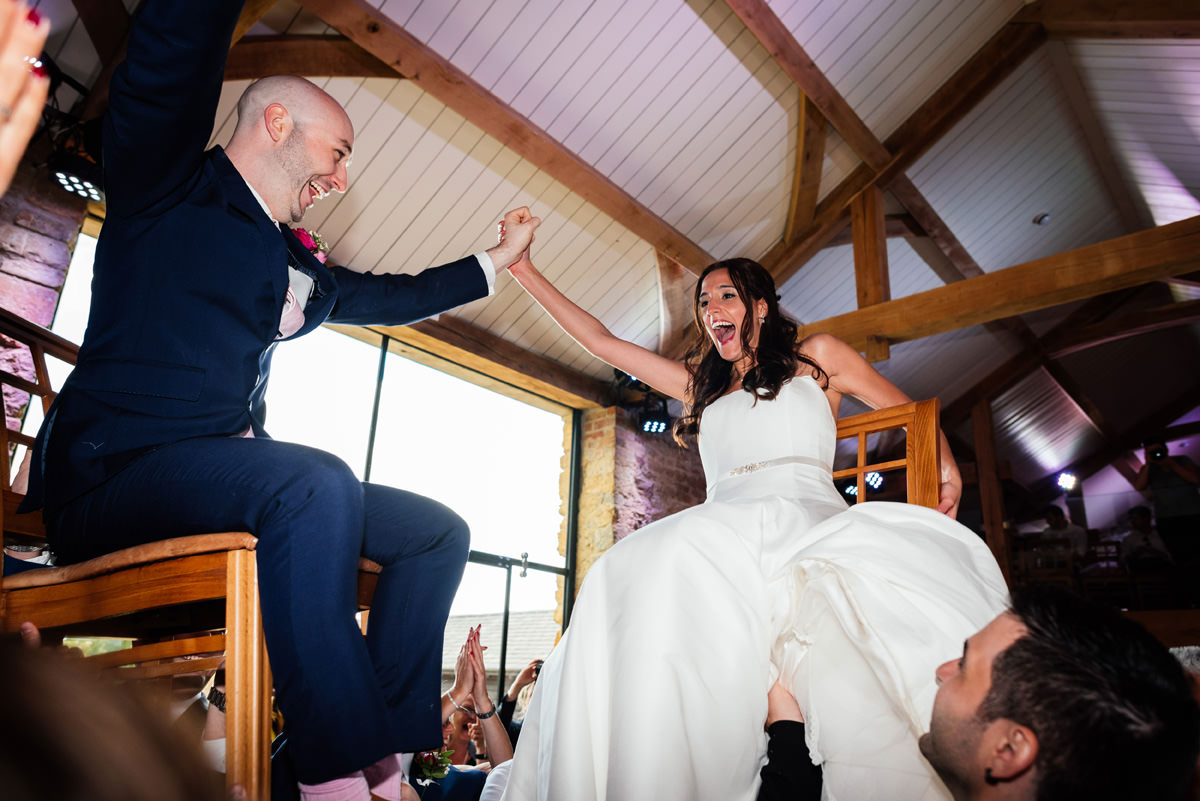bride and groom up on chairs for jewish dancing