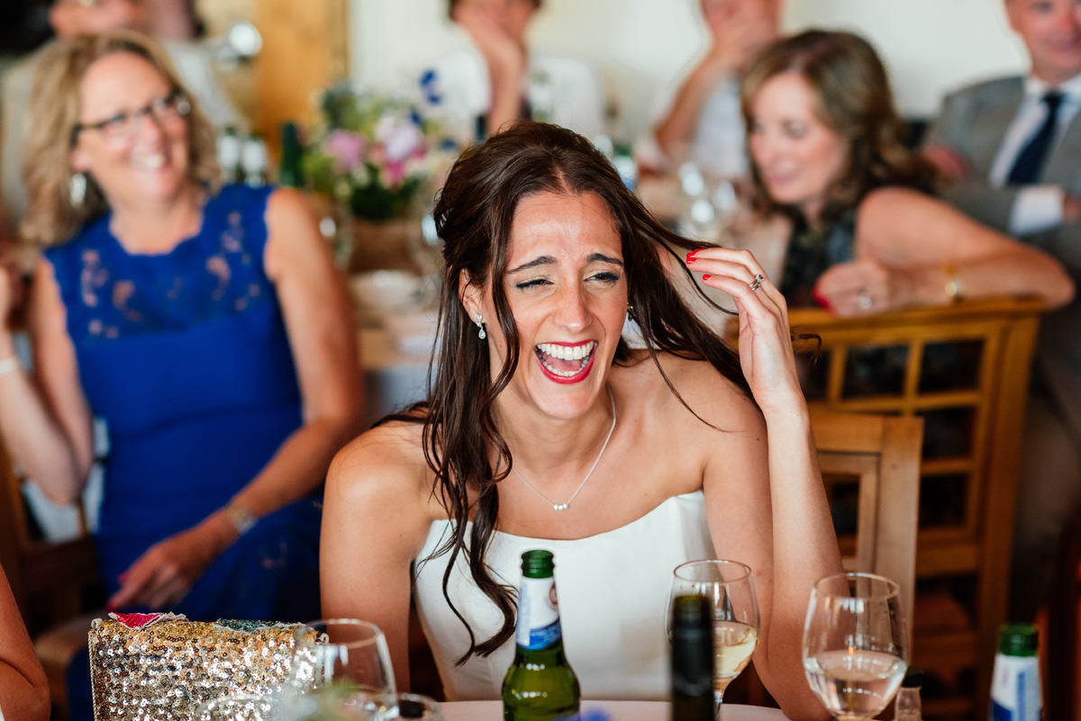 bride laughing at the wedding speeches