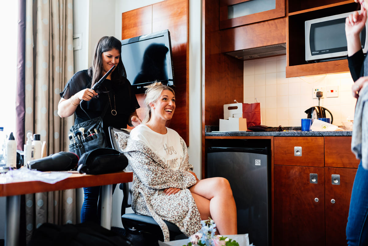 bride has hair and make-up in the morning of her wedding