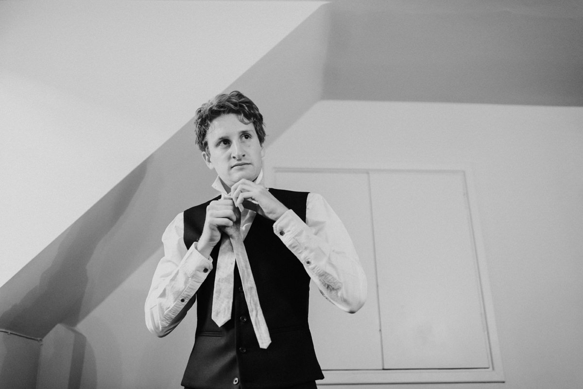 groom getting ready putting his tie on