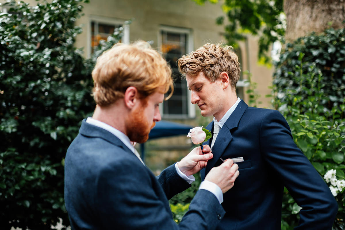 best man putting button hole on to groom