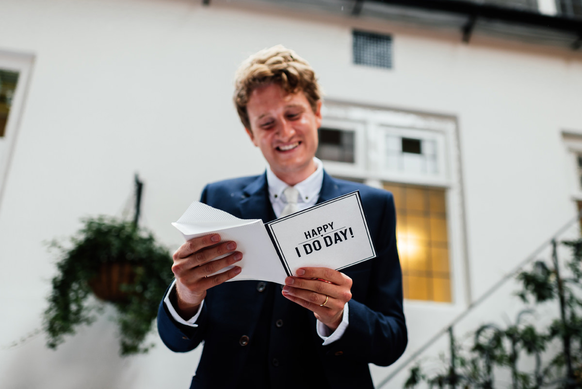 groom receives wedding card from bride