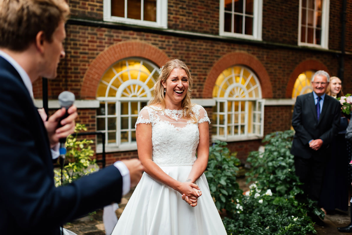 bride laughing at groom during speech