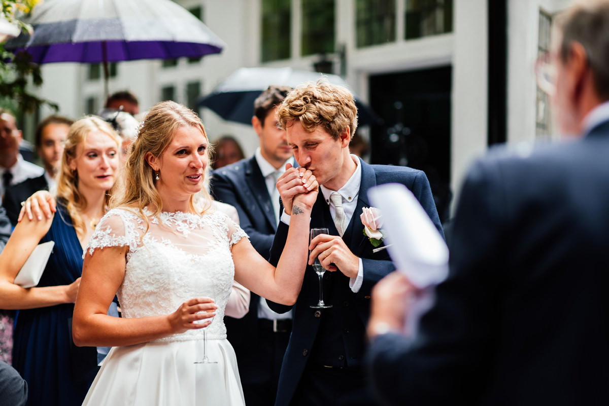 groom kisses his bride's hand during the speeches