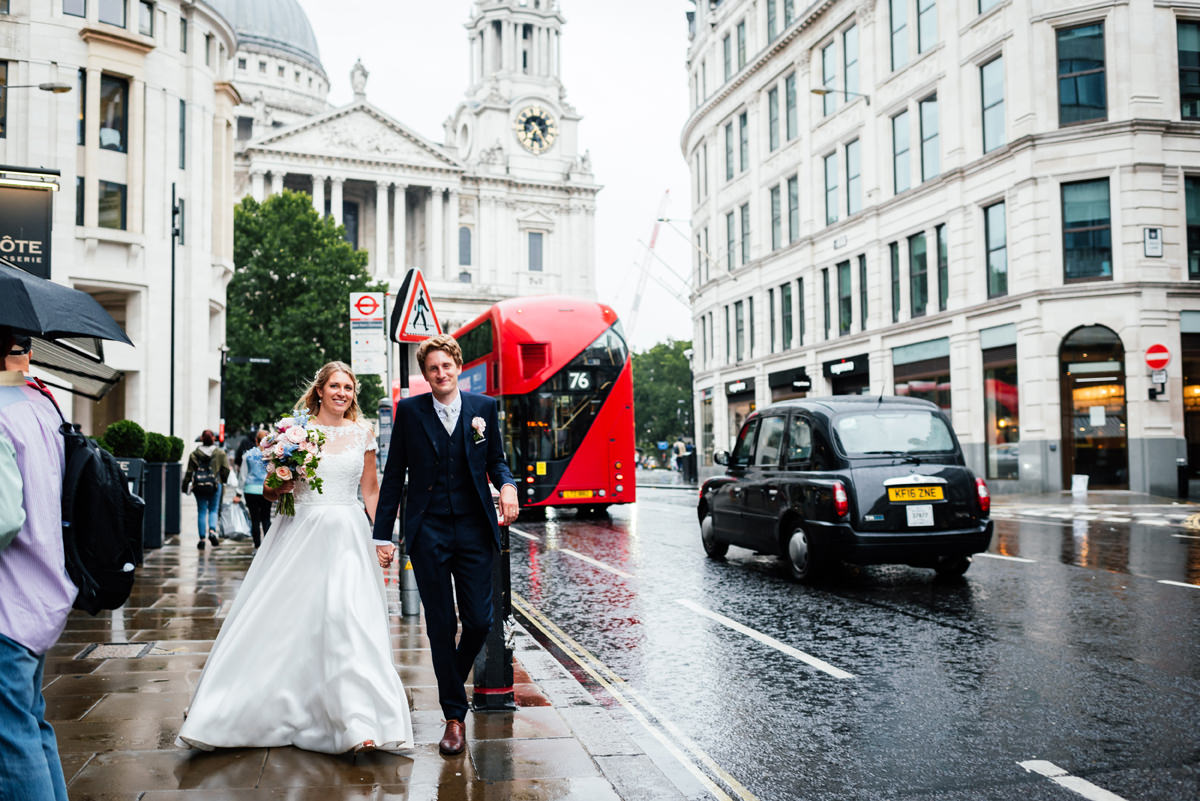 bride and groom walking down london street with st pauls cathedral behind them