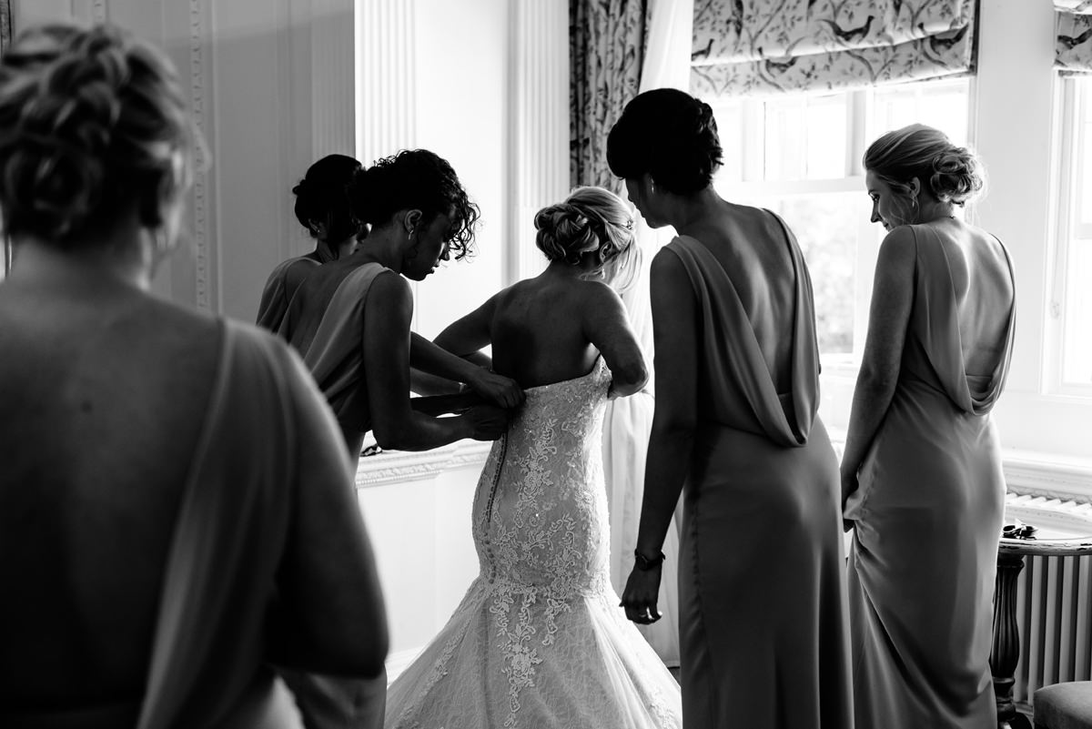 bride being helped into her wedding dress with bridesmaids