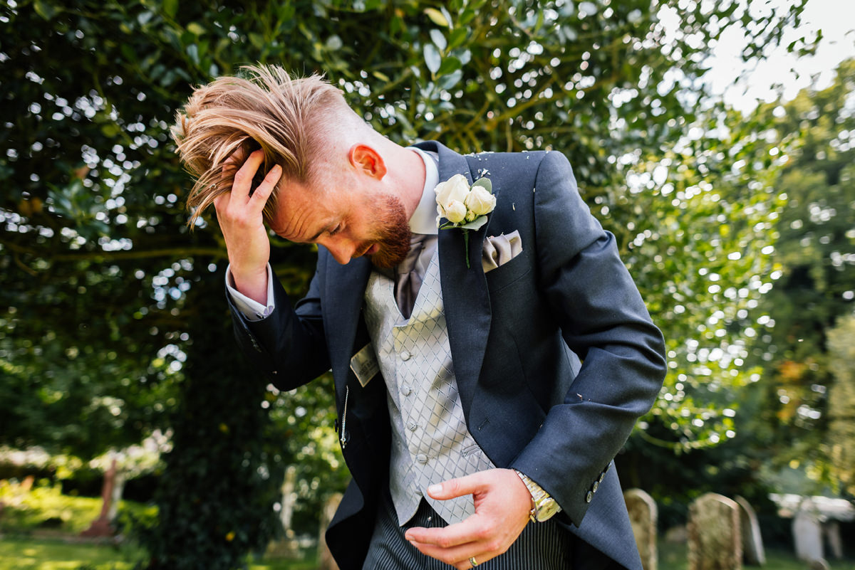 groom trying to get confetti out of his hair