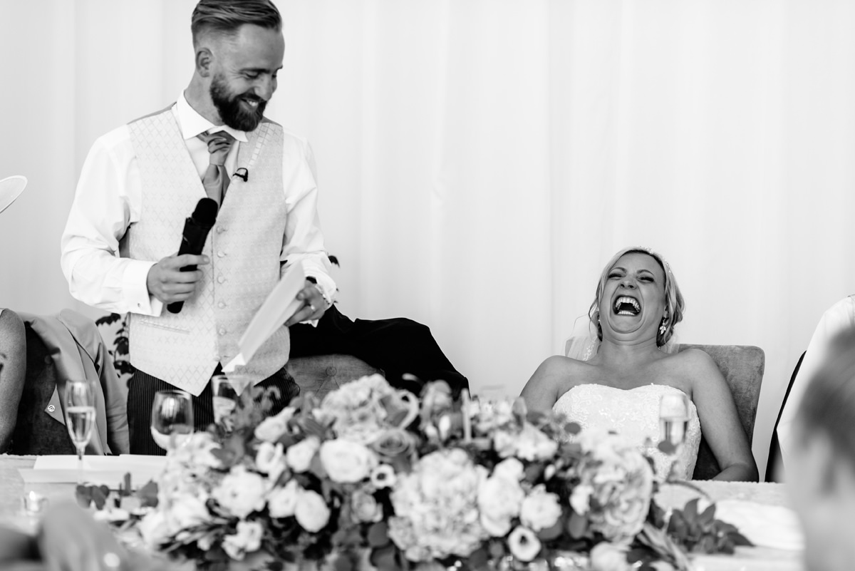 bride laughing at groom speech