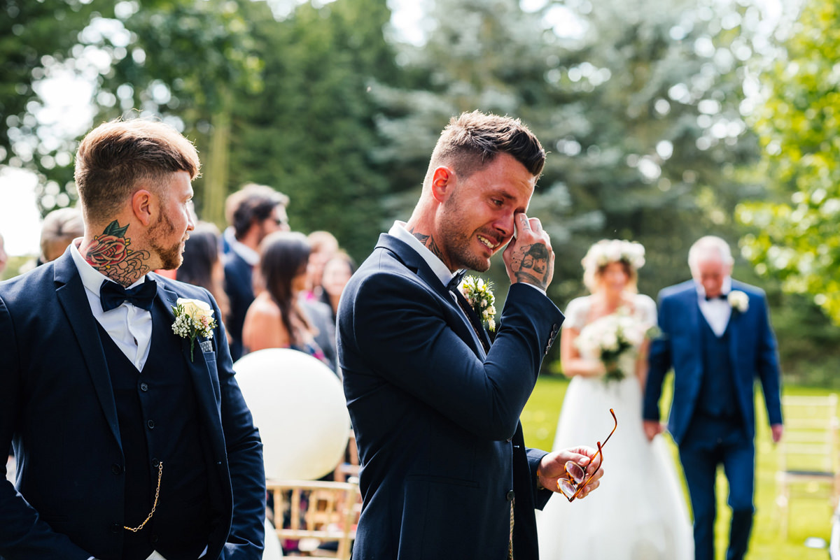 groom wipes a tear as his bride arrives