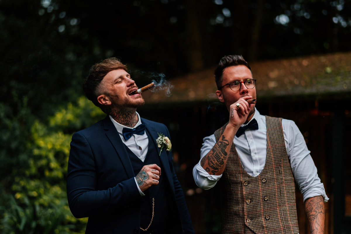 groom and best man smoking a cigar