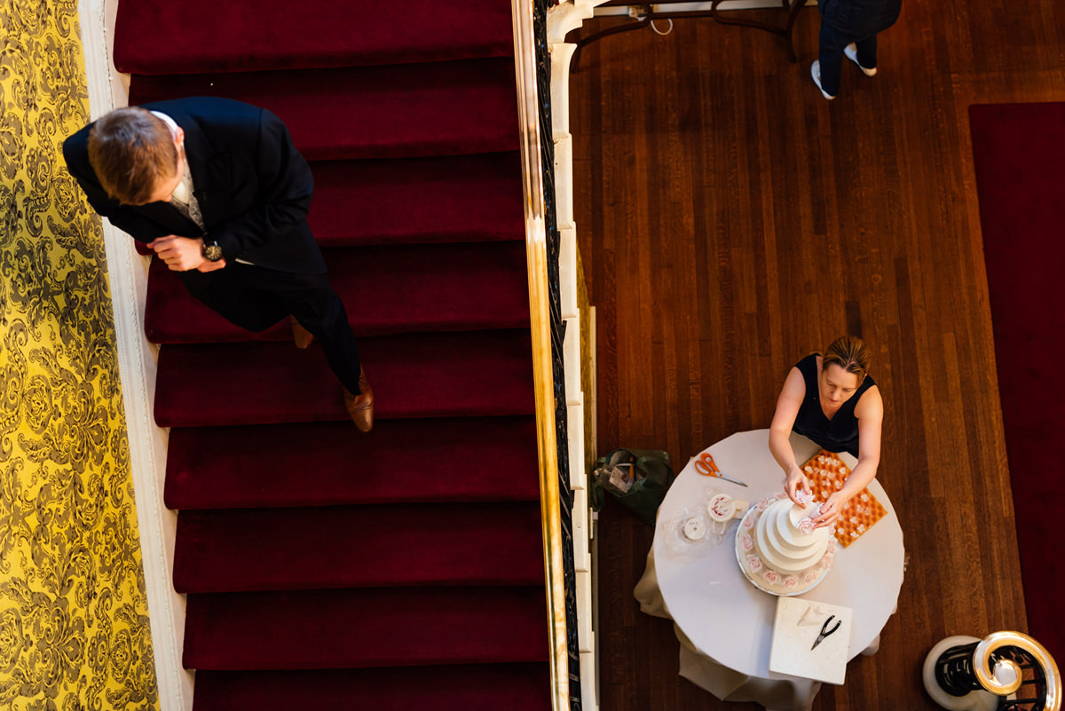 Groom walking down stairs whilst the wedding cake is put together