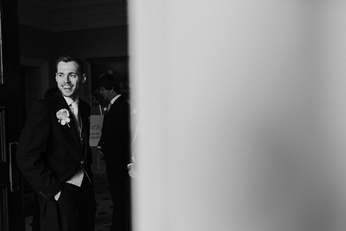 groom laughing whilst waiting for guests to arrive