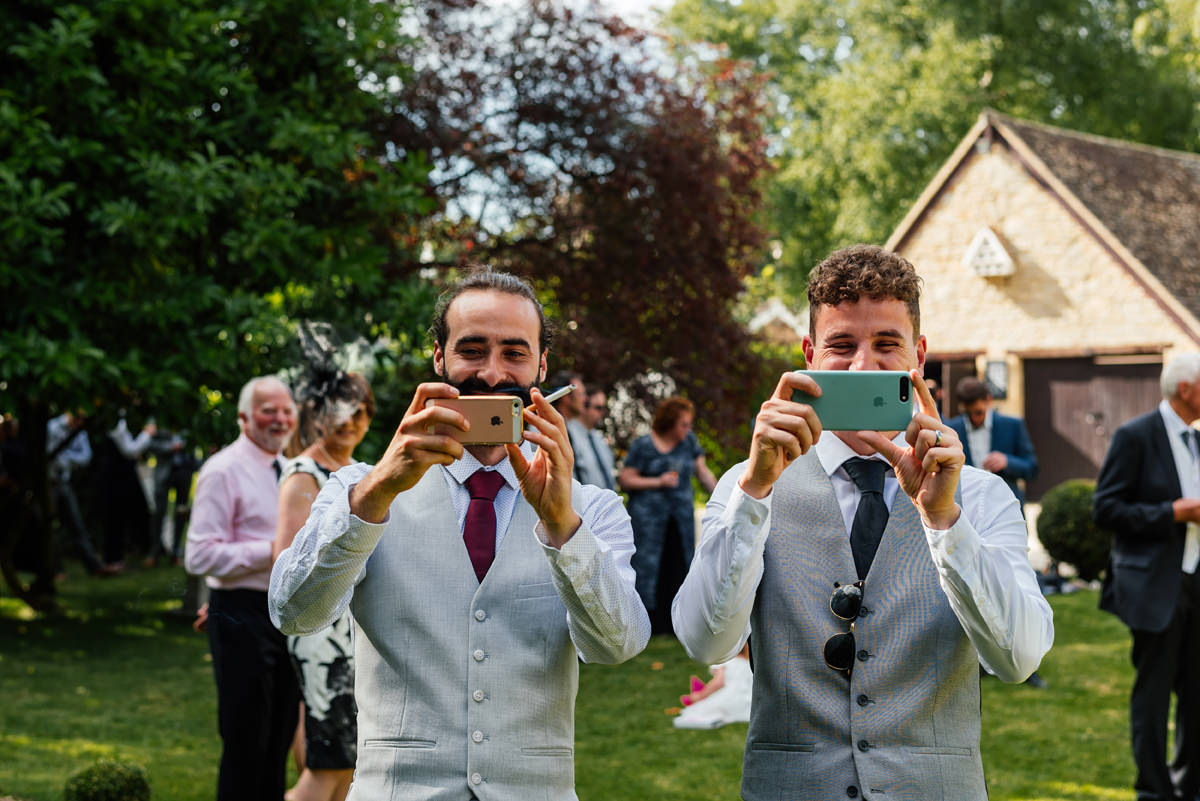wedding guests taking photos with phone