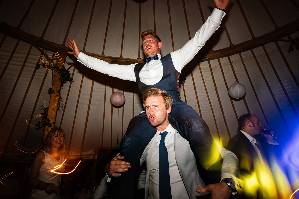 groom on the shoulders of his buddy